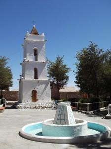 Campanario y fuente de color blanca en Toconao