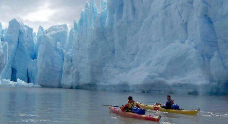 Dos viajeros navegan en kayak frente a glaciar en Torres del Paine