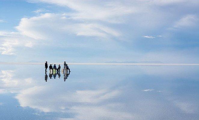 Viajeros se reflejan gracias al efecto espejo durante la mejor época para visitar el Salar de Uyuni