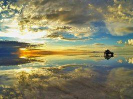 Reflejo del cielo sobre agua y un automóvil en Salar de Uyuni