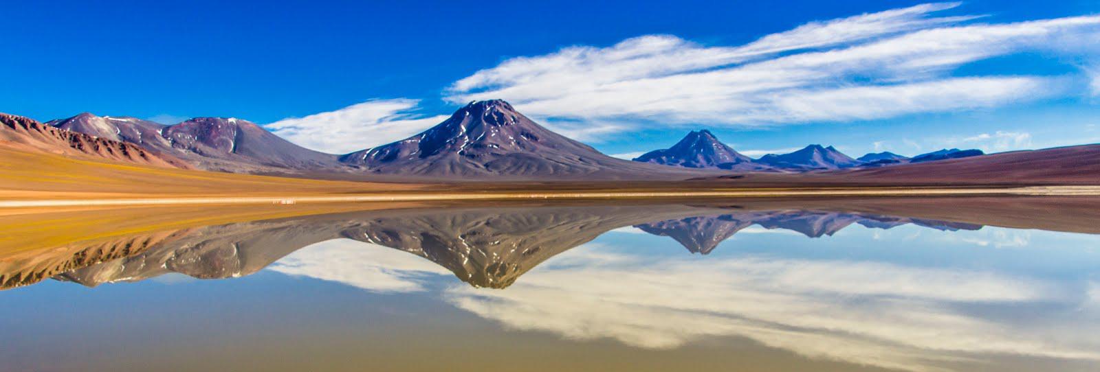 Volcanes frente a laguna reflejados en el agua