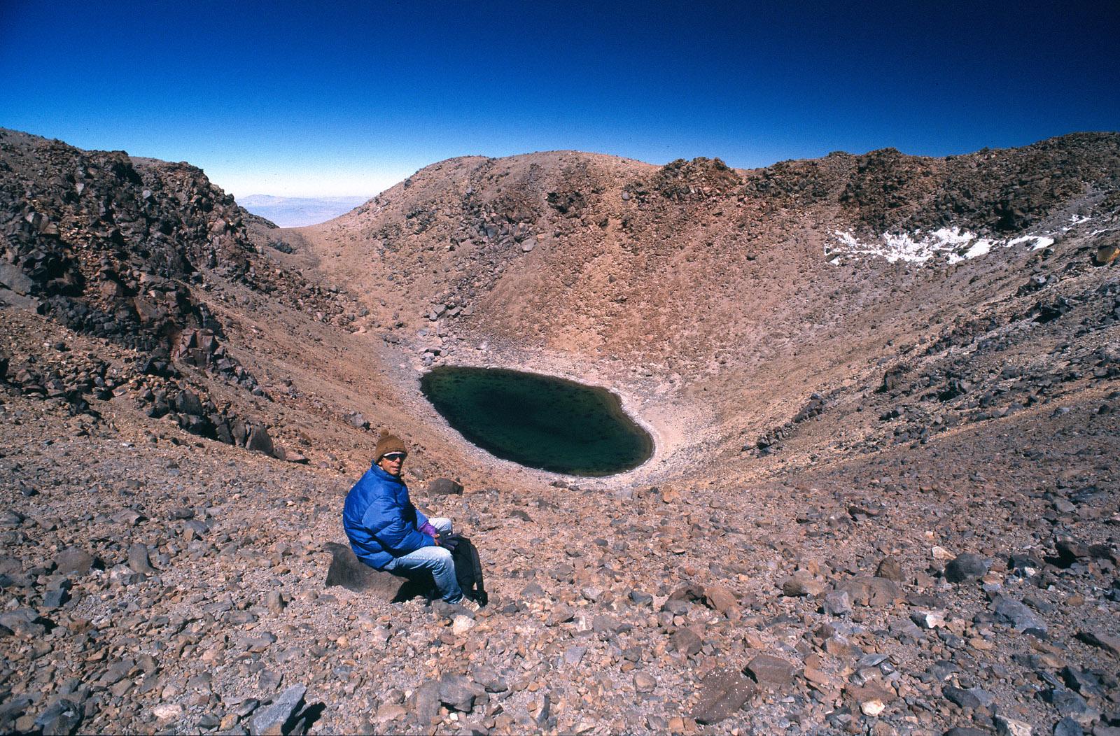 Hombre sentado frente a laguna en la cima de un volcán