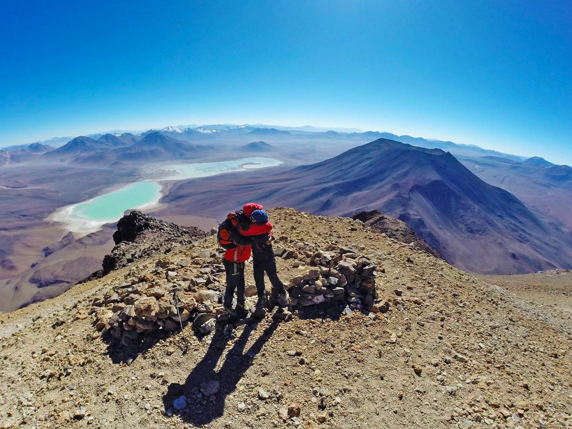 Dos escaladores se abrazan en cumbre con volcanes de fondo