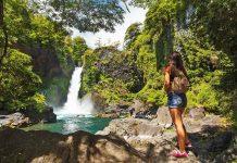 Mujer frente a cascada en el bosque