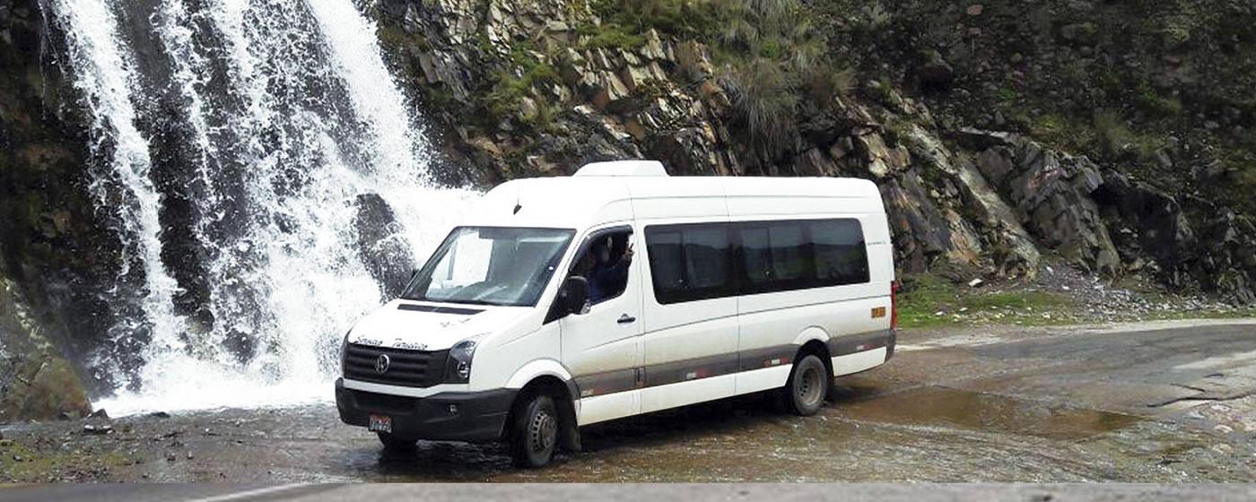 Minivan blanca frente a cascada