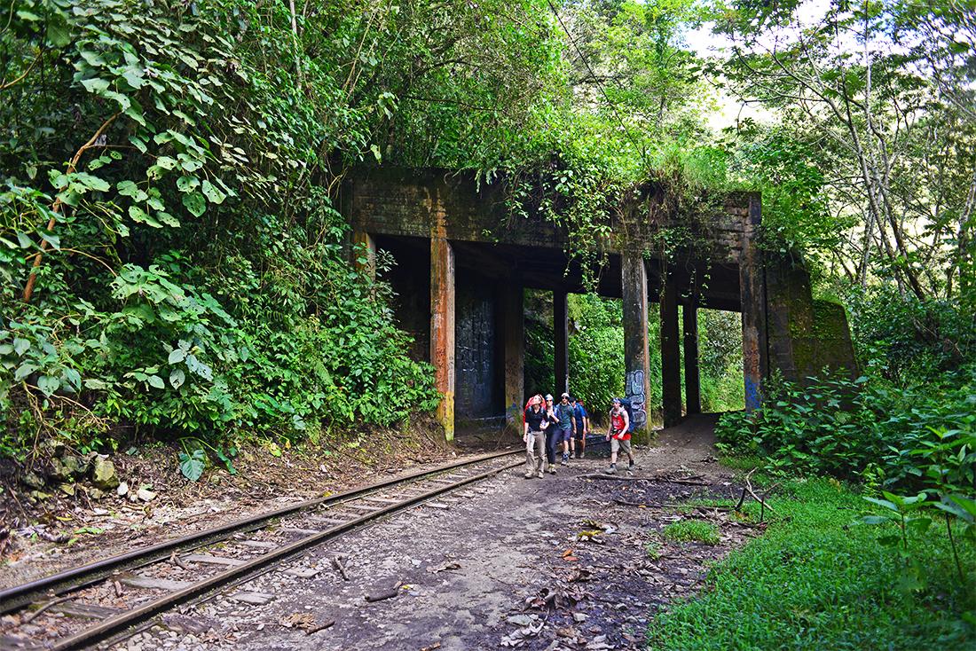 Viajeros caminando bajo puente en la selva peruana