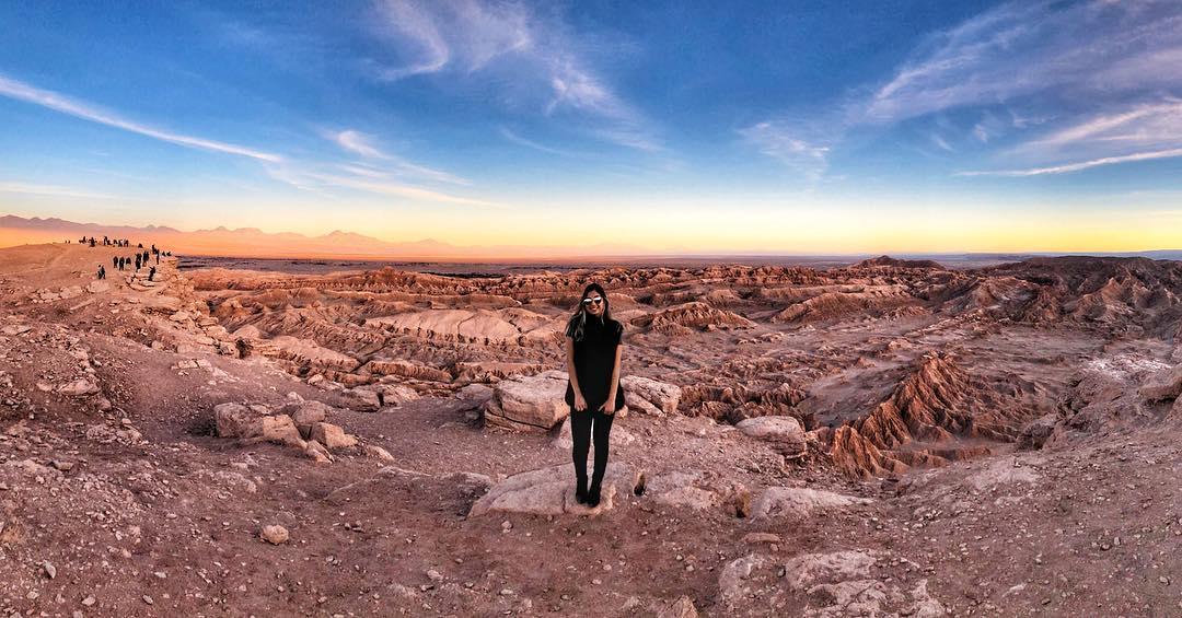 Viajera parada sobre valle rocoso en Atacama