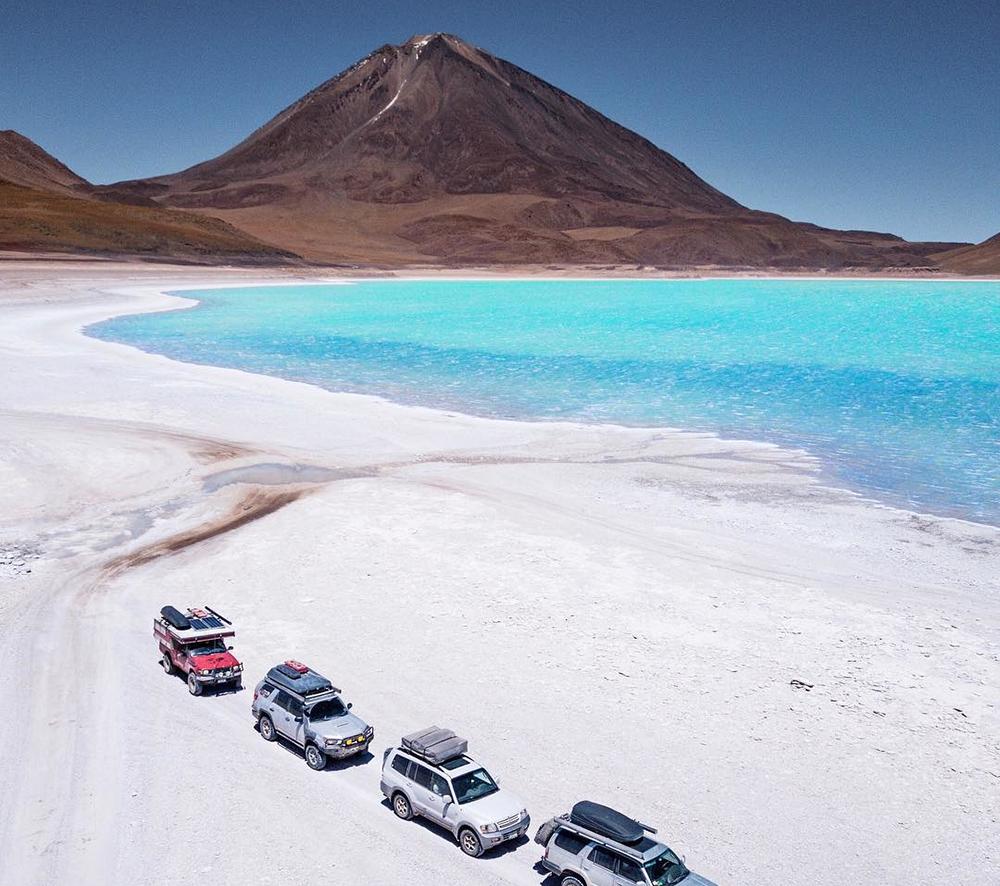 Vehículos estacionados al lado de laguna turquesa y volcán de fondo en Atacama