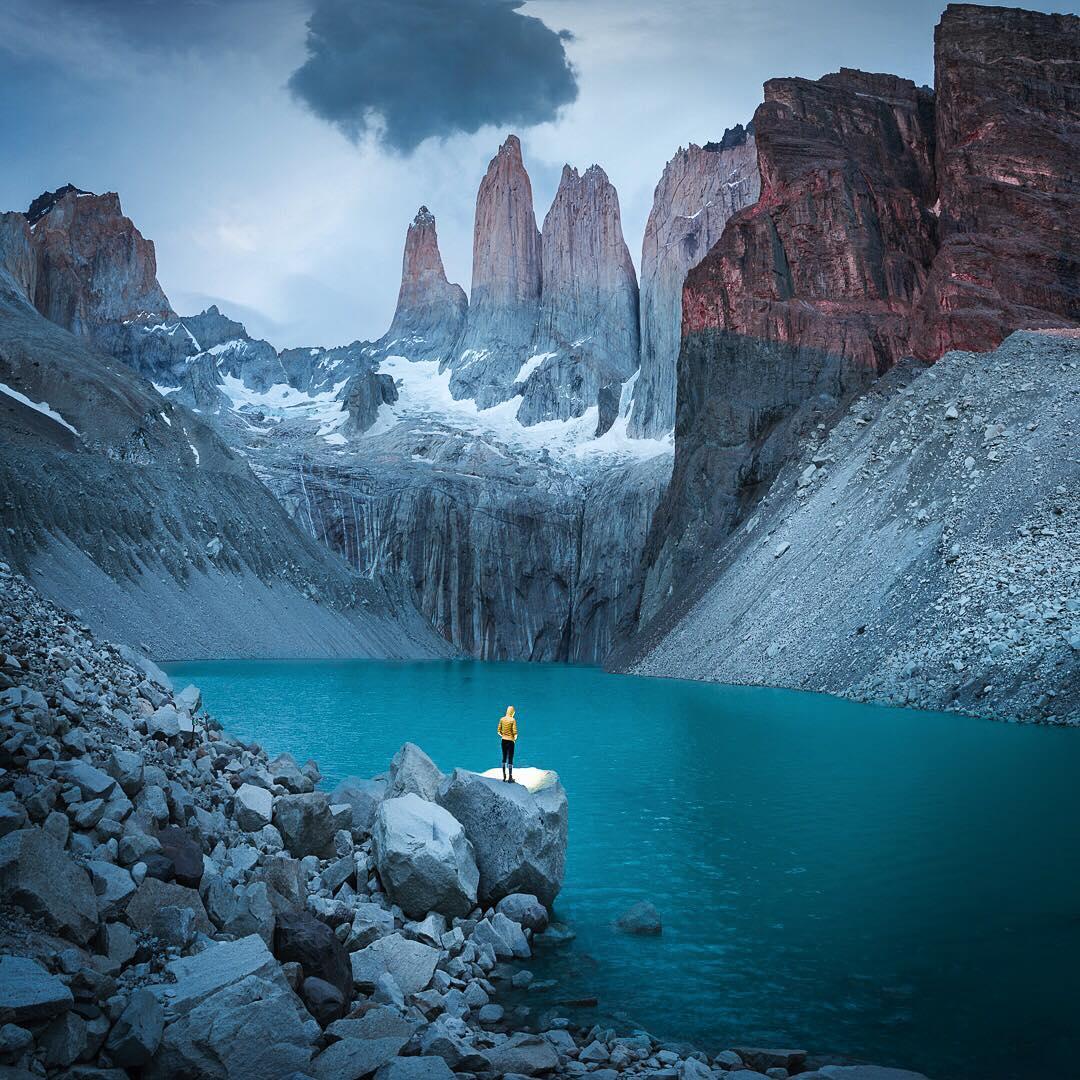 Viajero frente a la laguna y paisaje montañoso en Torres del paine