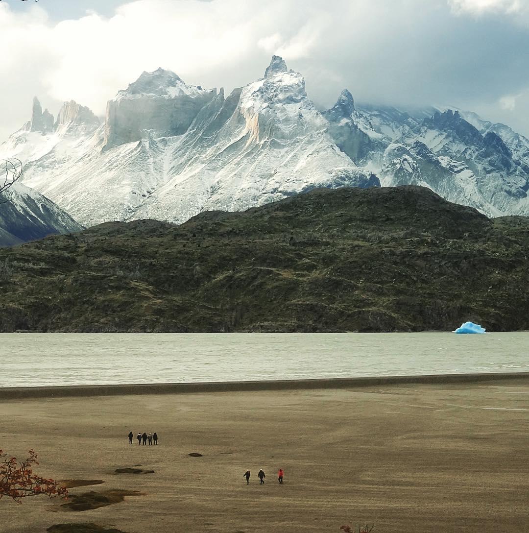 Personas caminando en playa patagónica, con témpanos de hielo y montaña de fondo