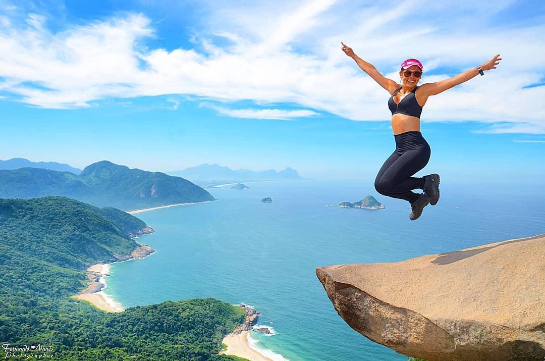 Mujer sobre roca con playa y bosque tropical de fondo