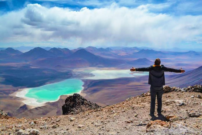 Viajero frente a paisaje desértico y laguna turquesa
