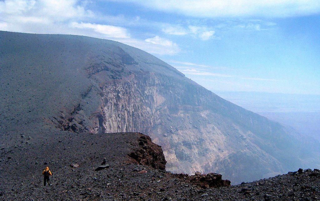 Viajero frente a crater de volcán