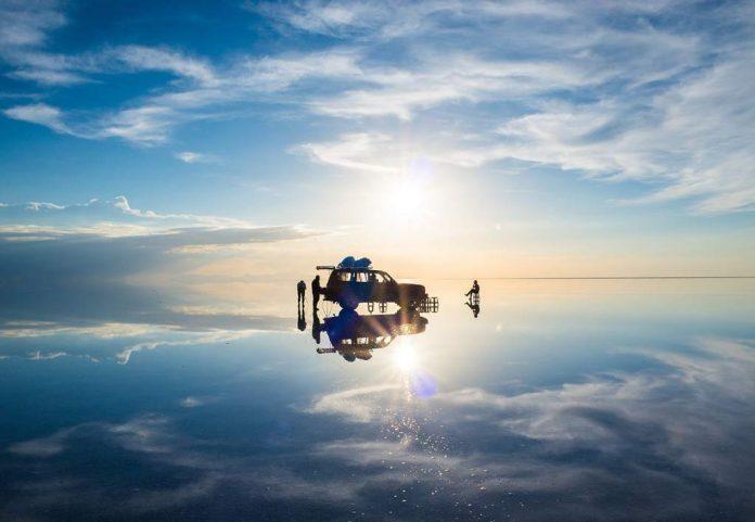 Automovil y viajeros sobre salar de uyuni durante efecto espejo