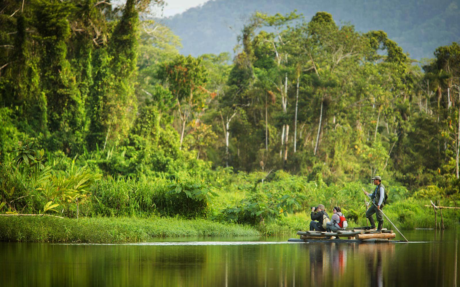 turistas en barcaza en el parque nacional del manu