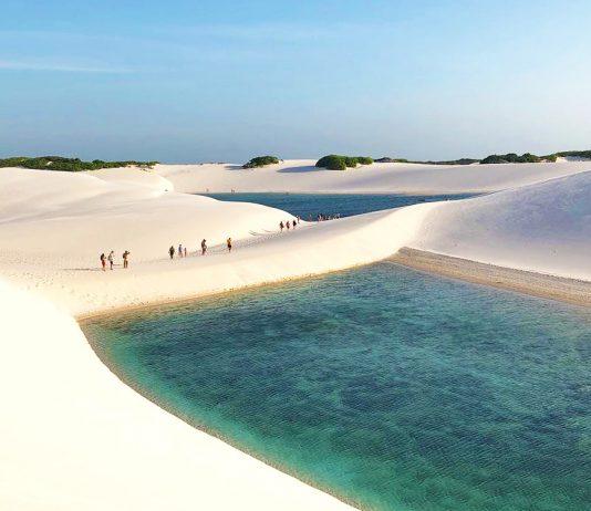 Viajeros caminando por desierto y lagunas color esmeralda en Brasil