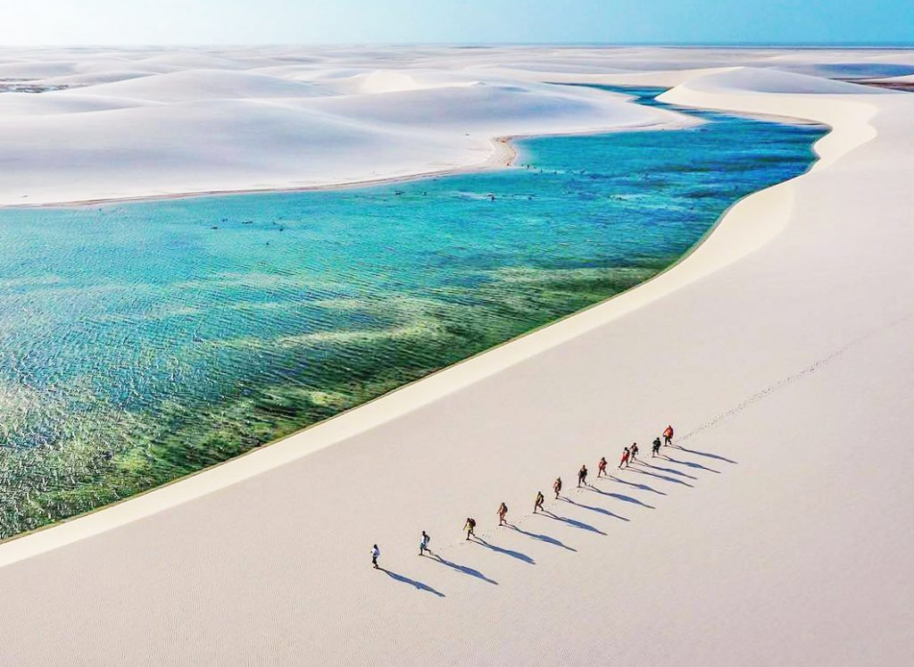 Viajantes caminhando no deserto com lagoas no Brasil
