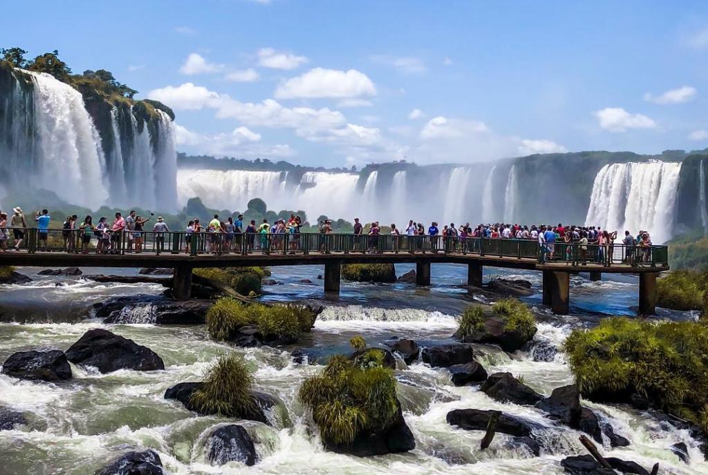 Viajantes andando por pasarelas frente a cascadas