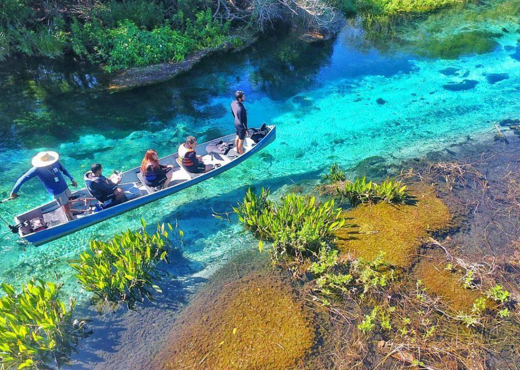 Viajantes navegando em cima do rio cristalino