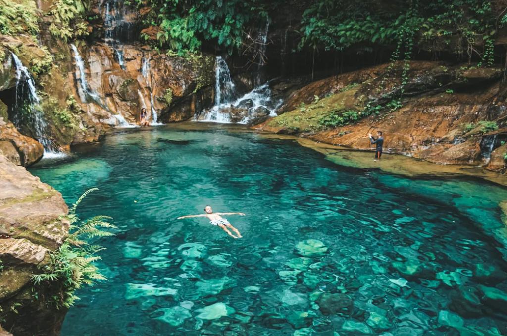 Viajante tomando banho em uma piscina natural
