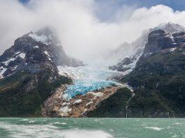Glaciar entre montañas y frente a lago