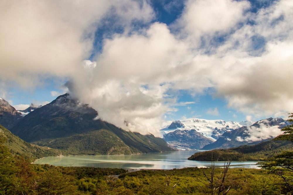 Lago patagómico debajo de montañas y nubes en circuito o