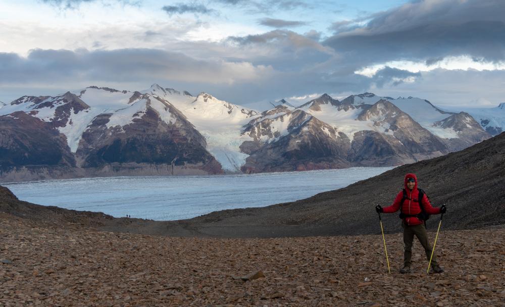 Viajero frente a glaciar y montañas en circuito o
