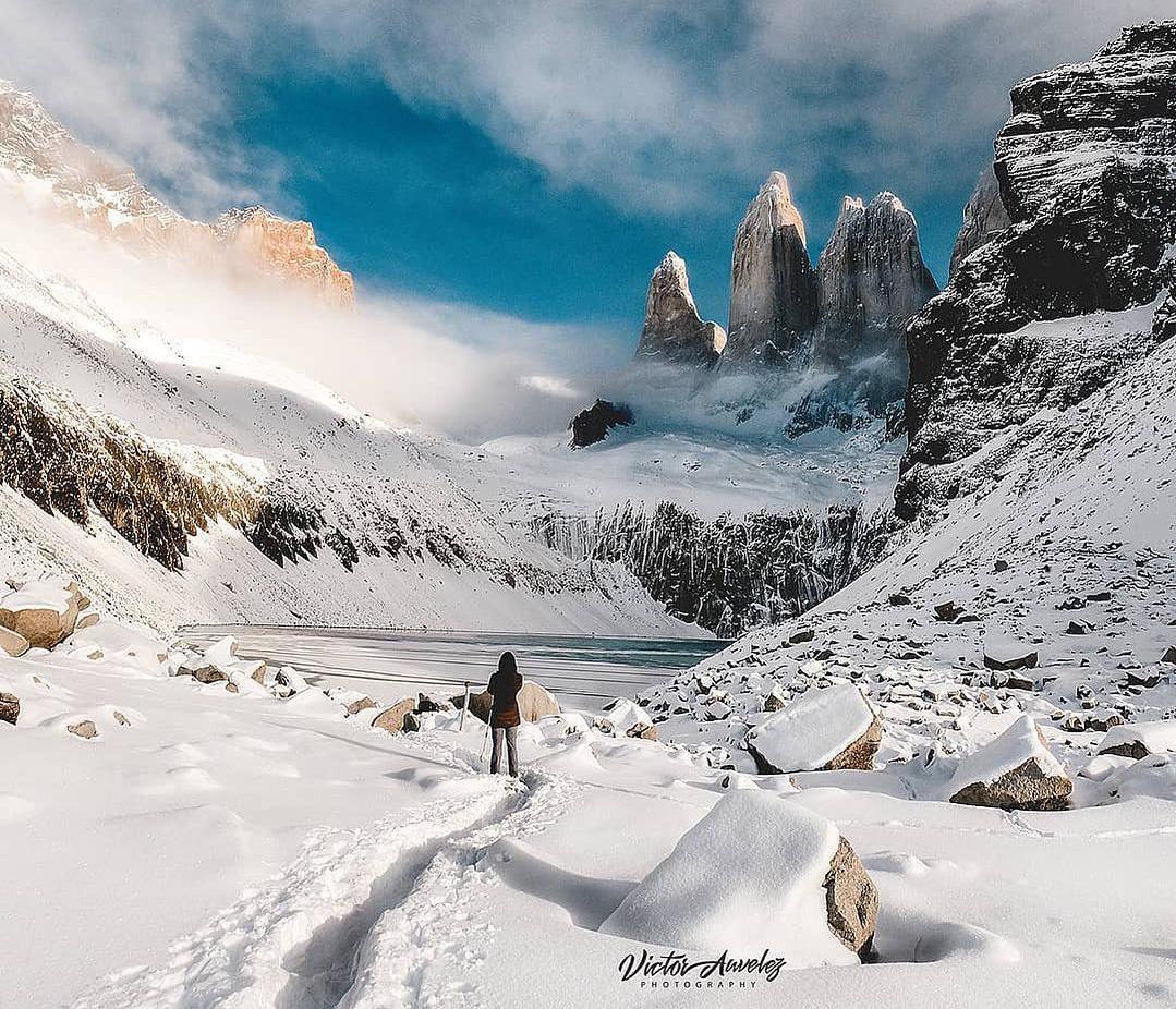 Viajera observando paisaje montañoso y nevado en Base Torres