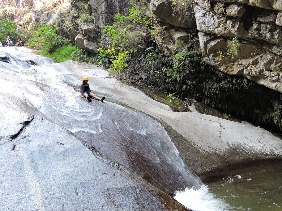 Viajera delsizandose por tobogan en rocas