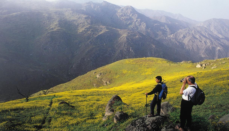Dos viajeros observan paisaje montañoso