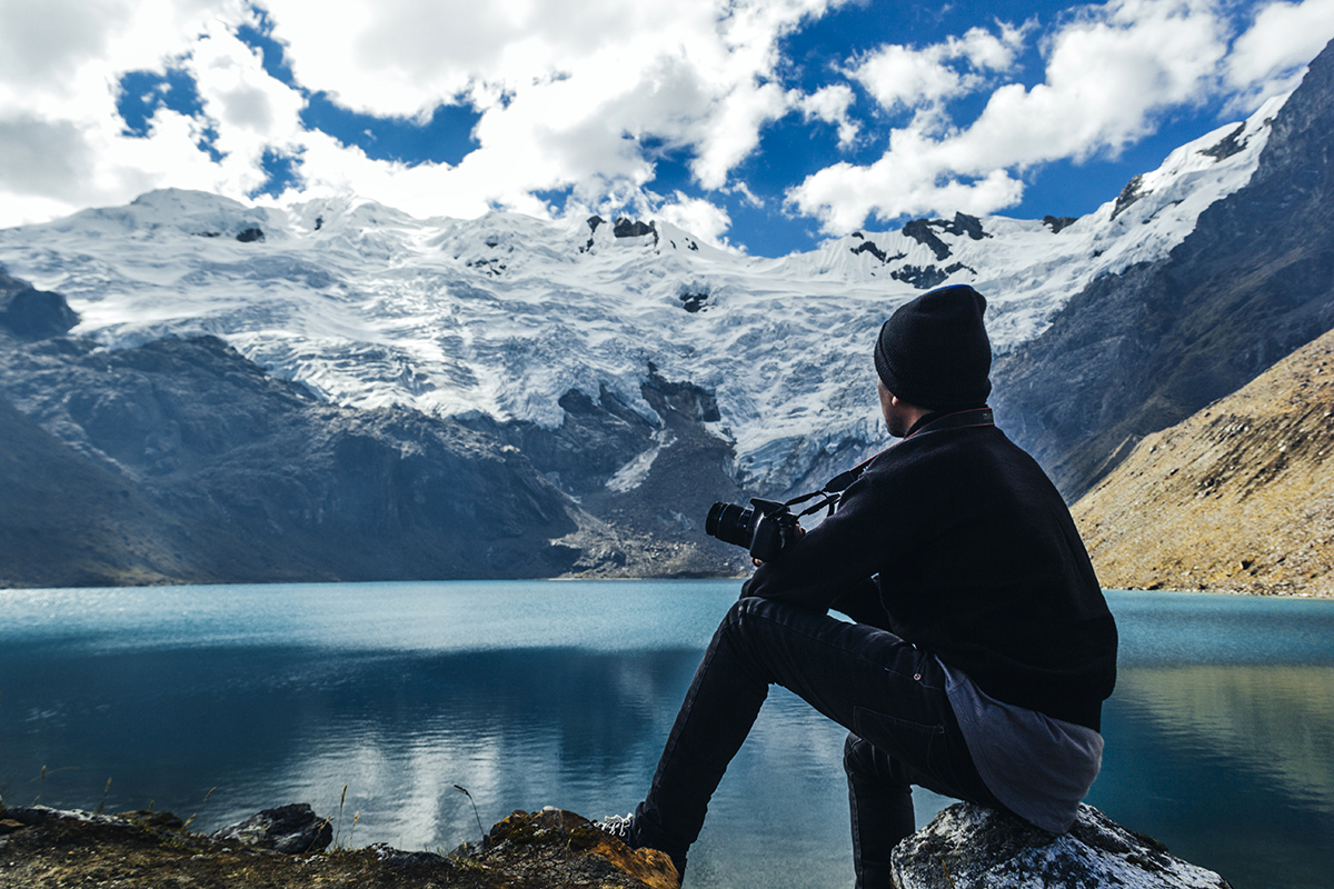 Viajero sentado frente a laguna y nevado