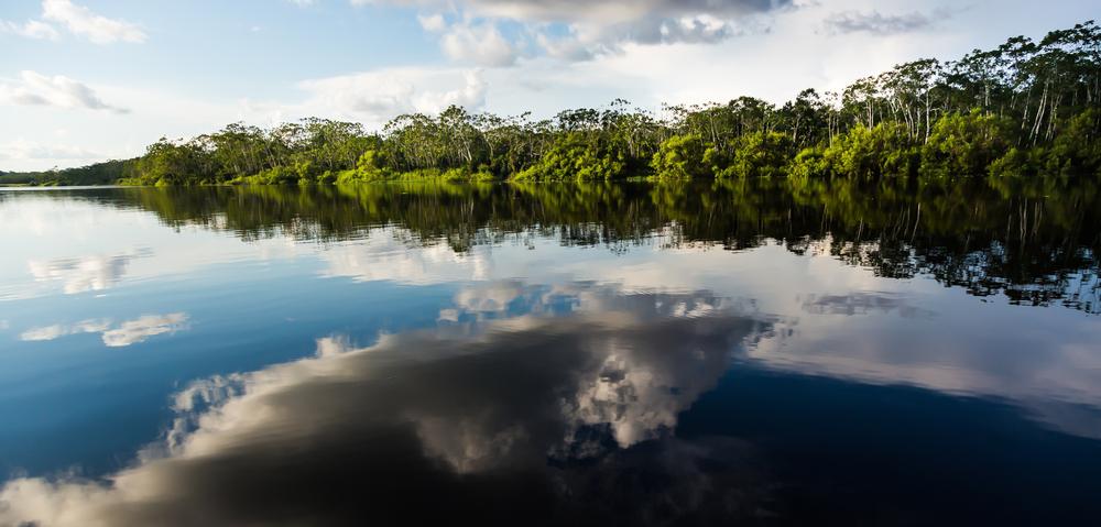 Reflejo de nubes sobre un río en la selva de puerto maldonado en perú