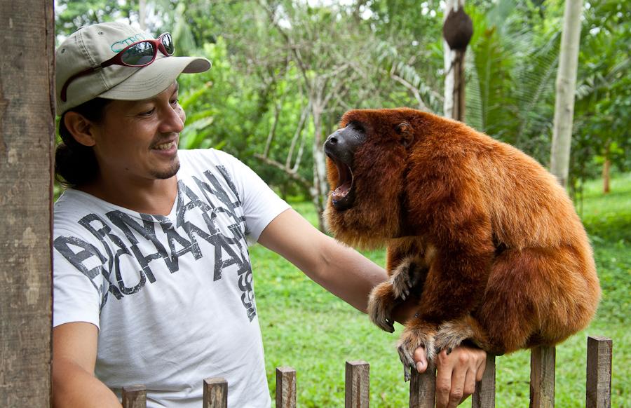 Hombre sosteniendo a mono en la selva peruana