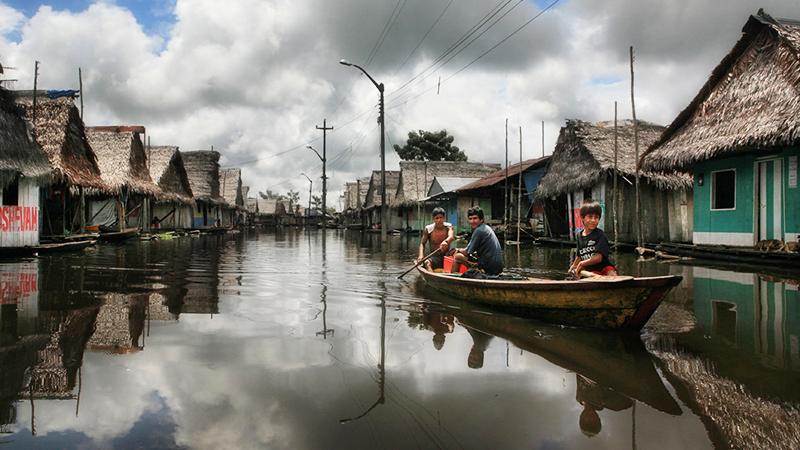 Grupo de locales navegando en bote por casas flotantes