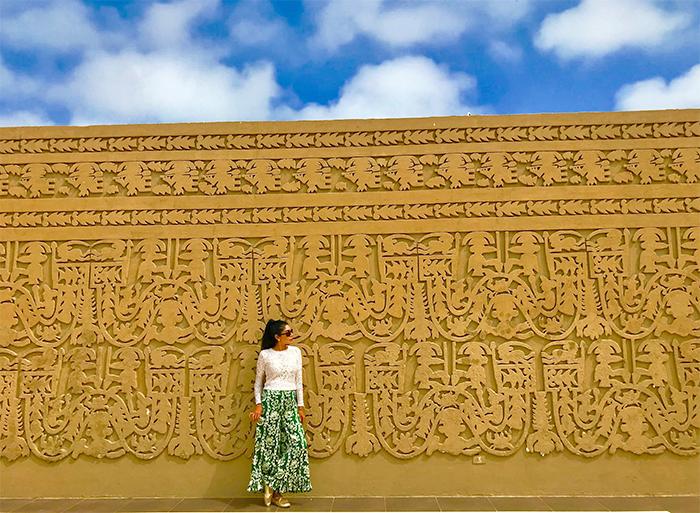 Mujer frente a muro en ciudadela de chan chan