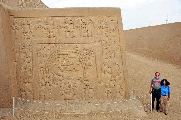 Dos viajeros junto a complejo arqueológico en Perú