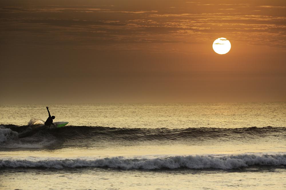 Surfista en el mar durante el atardecer
