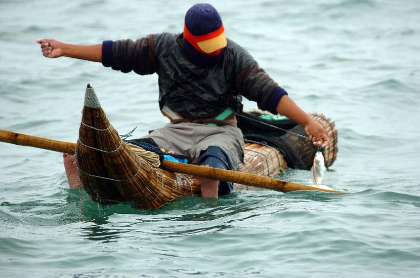 Pescador arriba de caballito de totora en huanchaco
