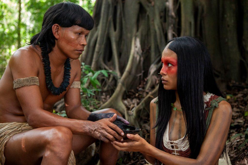 Pareja de personas indígena comparten un brebaje bajo un árbol