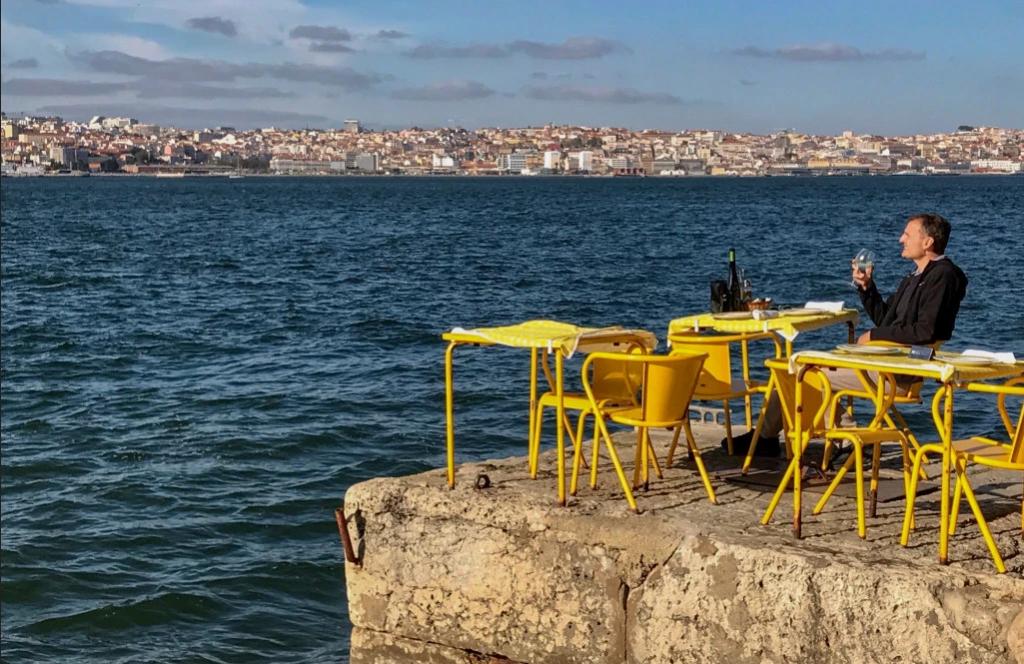 Hombre sentado en una mesa amarilla mirando la ciudad