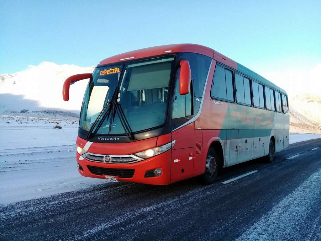 Bus rojo a travesando paisaje nevado