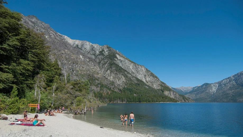 Personas bañandose en la playa de lago en Bariloche