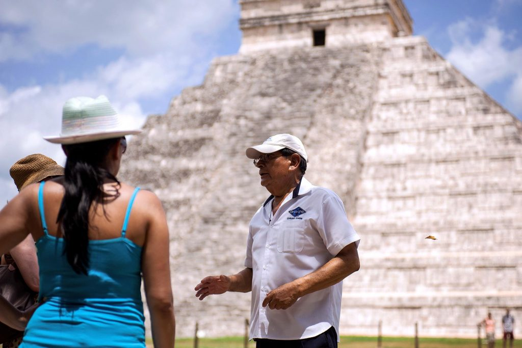 Guía turístico explica a viajeros en Chichen Itzá