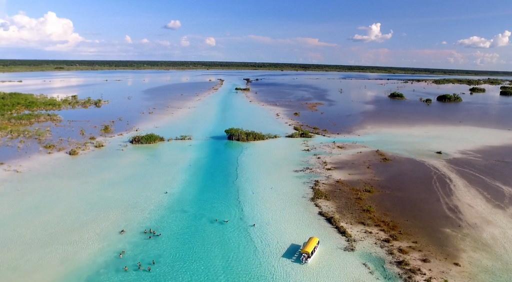 Pequeño barco navegando sobre aguas cristalinas en méxico