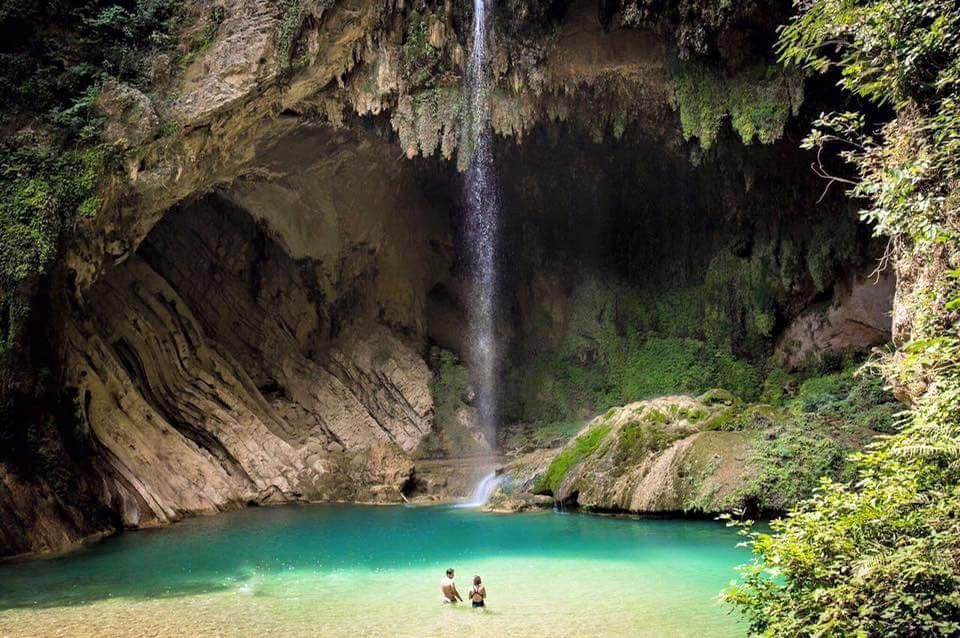 Dos personas observando cascada en una cueva en méxico