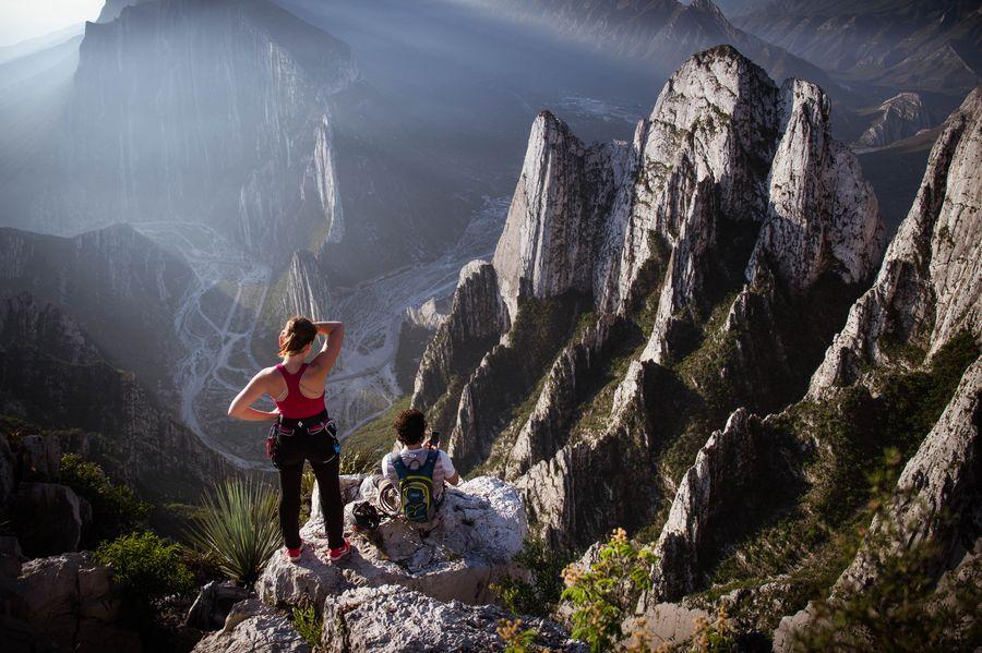 Dos viajeros arriba de un mirador en una montaña