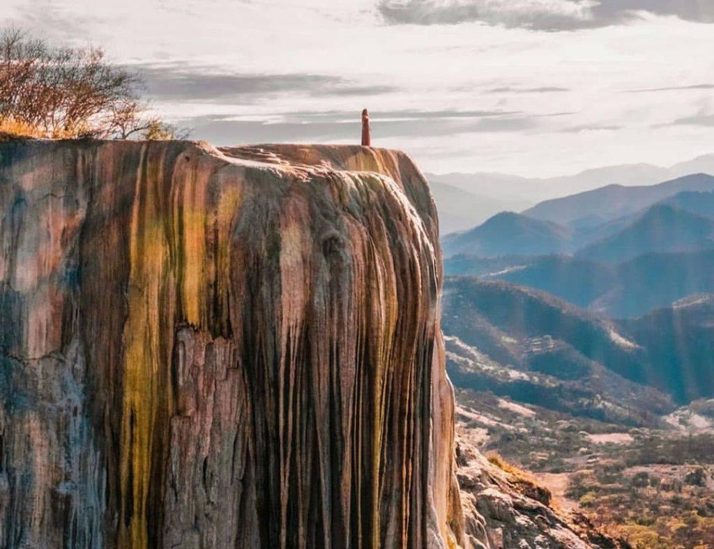 Persona observando paisaje desde cascada petrificada