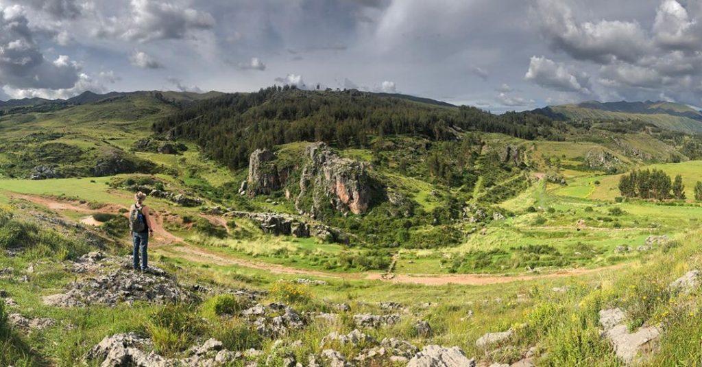 Viajero observando paisaje con mucha vegetación y rocas