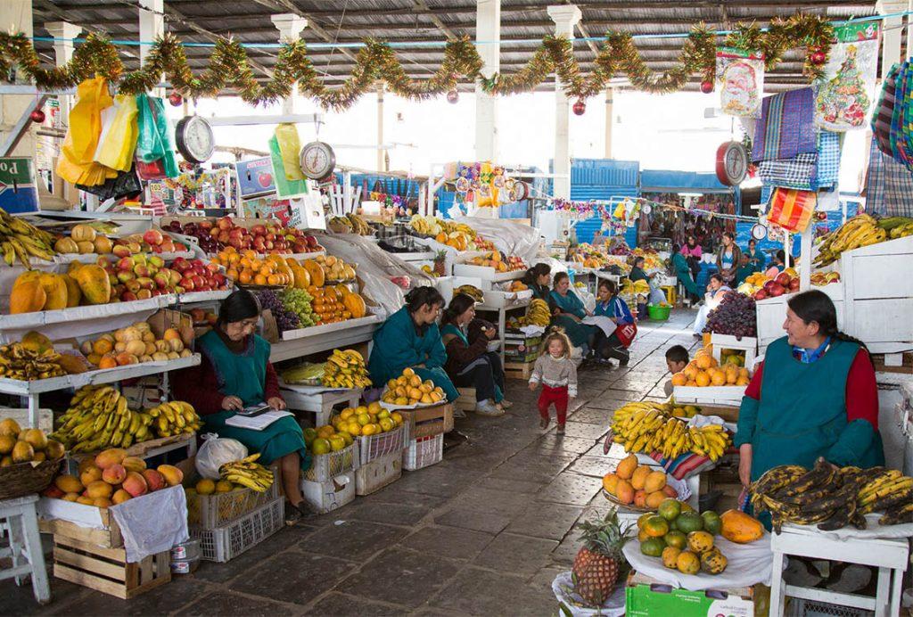 Feria de frutas y señoras sentadas