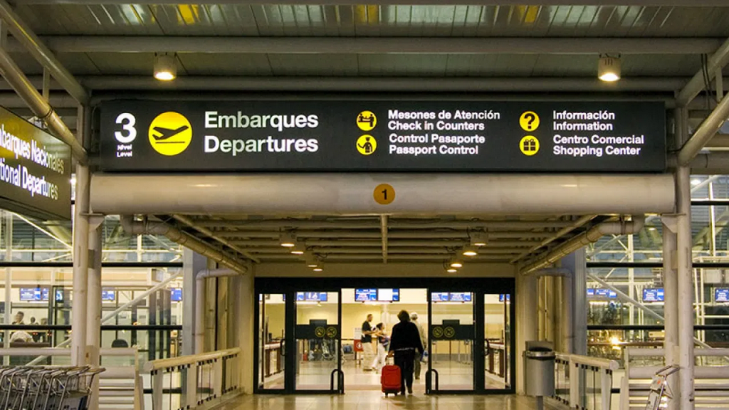 Persona entrando al aeropuerto de Santiago en la noche